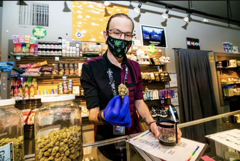 Budtender Joseph Domalick holds up a marijuana nug at the Basalt store